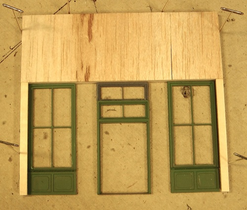 This photo shows the front of the building with the two large windows and the door frame in their relative positions.  Because I am going to recess the door, it will sit back a bit on the finished store, and be connected to the two large windows by two more slender windows positioned at an angle.