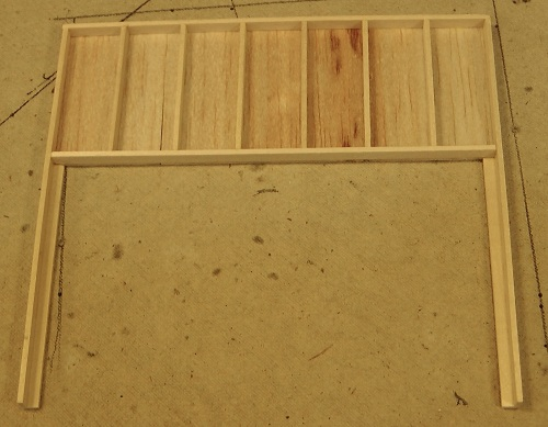 I'm going to used board-by-board construction, as I did with the Eureka store.  Here is the backside of the false front for the store with basswood studs and balsa wood sheathing.