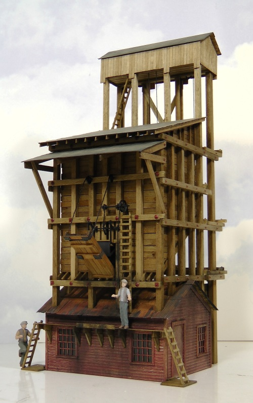 """The same side from the other corner. The figures are pre-painted pewter from Artistta.  The mechanism to operate the coat gate and chute were the most complicated to assemble.  The worker standing on the narrow platform would pull on the chain (visible just over his right shoulder) to activate the gate (heavy black curved metal piece behind the chute) which would open and release the coal.  The drawbridge-like chute was lowered separately.  I weathered the coaling tower with black """"soot"""" powders in areas where coal dust would fall."""