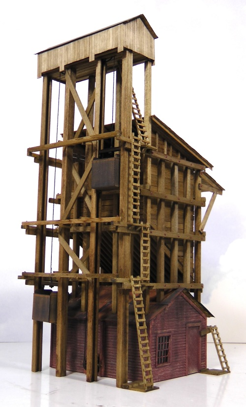 The two lift buckets riase and descend in opposition to each other to balance the weight.  They go into the pit to get the coal, and discharge it at the top of their travel into the large wooden storage bin that comprises the bulk of the tower.