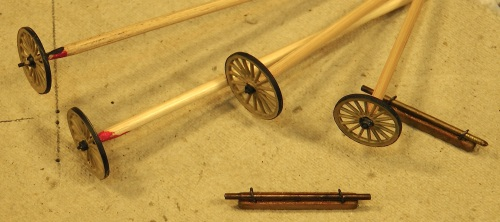 The wheels are Grandt Line Popcorn Wagon wheels.  When I try to paint just the spokes on these tiny wheels, I use bamboo shish-ka-bob sticks.  The pointed end usually wedges into the axle hole nicely, and I hold the blunt end in my teeth, leaving both hands free to manipulate the brush and wheel.
