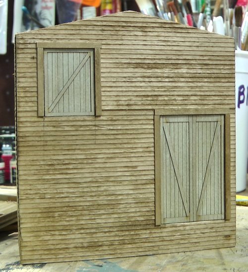 I used clapboard siding, a Grandt Line window and door for the office, and Rusty Stumps laser cut doors for the back.