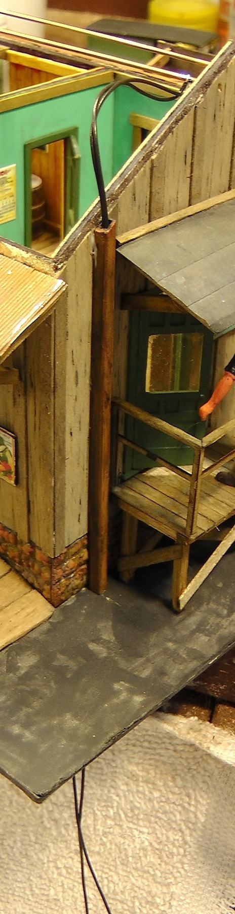 I ran the feed wires to the bus through the base of the freight house model, and up a rusty exterior conduit.
