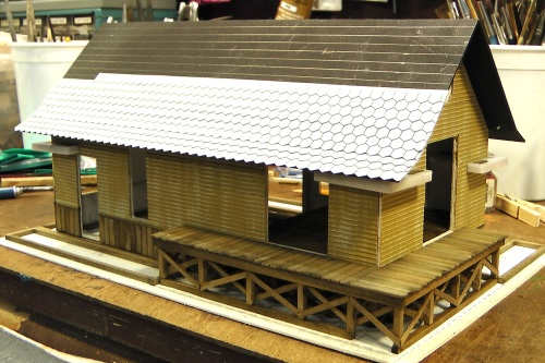 I gave the roof matte board a coat of Testor's Flat Black spray paint.  This will help a little with warping.  After that had dried, I started applying Branchline Trains French Style Victorian Shingles.  These will get painted and weathered eventually.