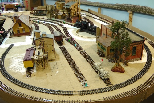 In this view from the other end of the roughly 4x8 ft. table, you can see the trolley track (standard HO Code 83) that I re-routed inside the turn back curve of my Micro-Scale Code 83 On30 track.