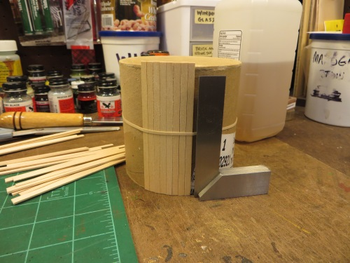 I sealed one end of the tube with card stock, and measured how many basswood strips would be needed to enclose the tube,