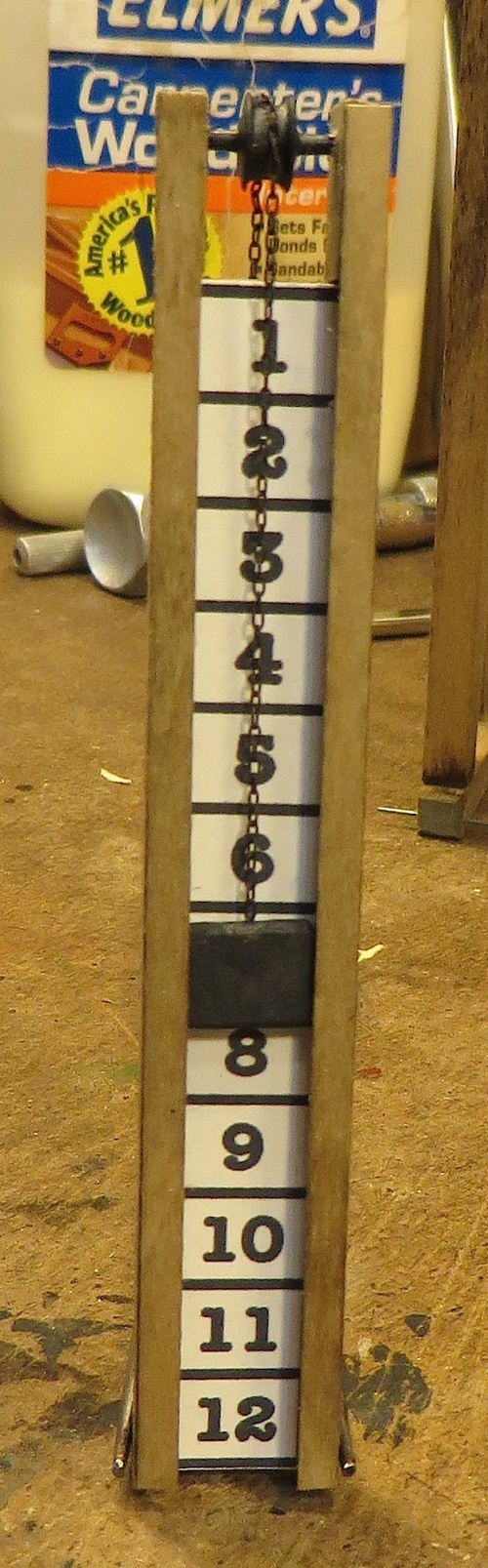 Here is the completed water level gauge.  The pulley at the top is made from an N scale wheel set. I cut it in half at the axle center, filed the axle points flat, and glued it back together with the wheels facing each other.