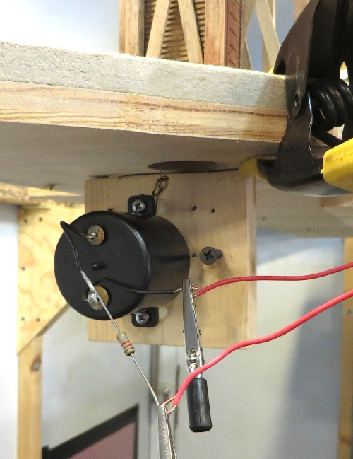 I drilled an inch and a 1/4 hole in the layout, and mounted a SwitchMaster switch motor beneath it on a piece of 1 x 4.  The mounting legs on the motor form one limit to the pivoting throw rod, and the dry wall screw to the right of the motor