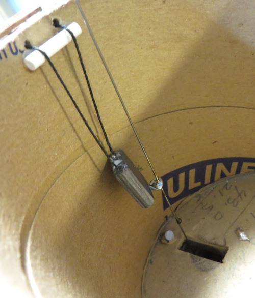 """The actuating rod is soldered to a small screw eye secured to the lead counter-weight inside the tank.  The little piece of styrene tubing helps to keep the """"cable"""" from dragging on the holes through the tank side."""