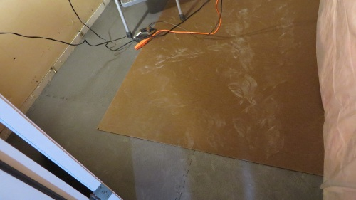 The concrete floor is covered with quarter inch thick, interlocking rubber mats, and eight inch thick tempered masonite.