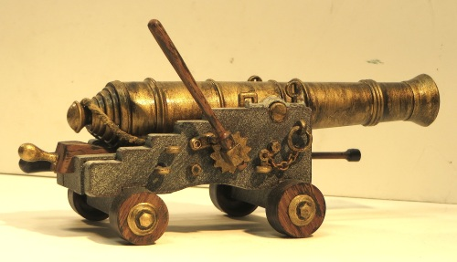"This model of a naval 24 pound cannon is by Palmer Plastics. It is roughly 7"" long by 3"" wide, but the exact scale was not specified. Plastic models present some different challenges from wood and brass kits, namely that the raw plastic has to be painted to look like other materials. Here the elevating block, the wheels and the ratcheting handle are painted like wood, the barrel is made to look like brass, and the cannon carriage like heavy cast iron. Everything here started out as plastic, and was assembled with Plastruct Plastic Weld solution."
